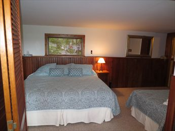 Open lower level bedroom with 2 twins and king with tv, walk out to yard