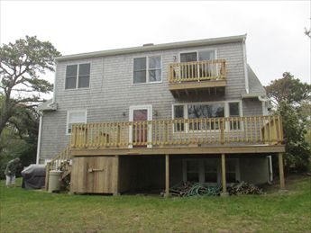 Back of house with large deck and 2nd floor balcony